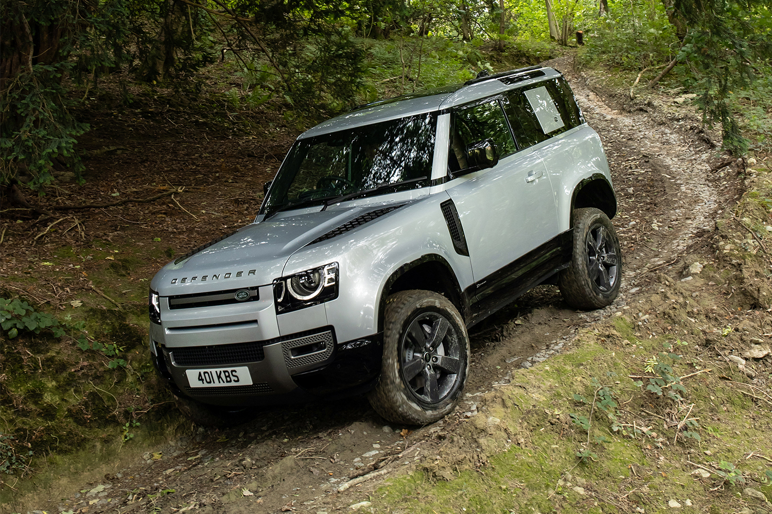 The 2021 Land Rover Defender 90 driving down a trail in the woods. We reviewed the luxury two-door SUV after test driving it in August 2021.