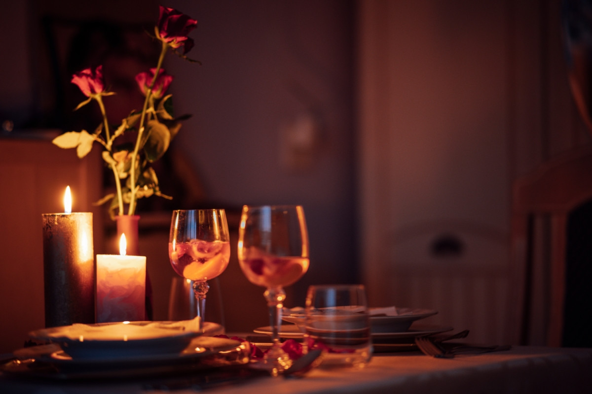 Romantic candle-lit dinner with wine glasses and roses
