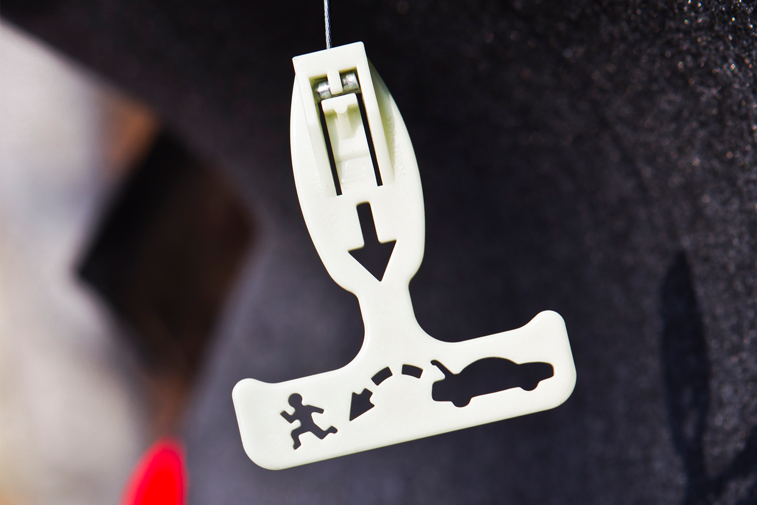 A glow-in-the-dark trunk release handle in the back of a car. After Janette Fennell was kidnapped, she advocated for the safety feature to be mandatory.