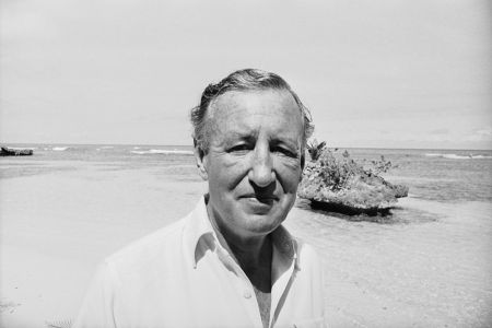 A black and white photo of author Ian Fleming on a beach. We take a look at how his wartime espionage work influenced writing his James Bond books.