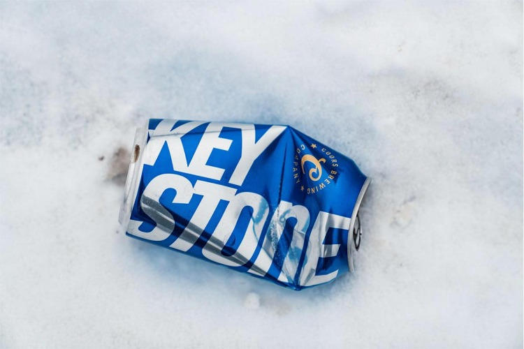 A crumpled aluminum can of Keystone beer near an ice fishing spot in Northern Minnesota in winter. Keystone is an alcoholic beverage made by the Molson Coors Brewing Company.