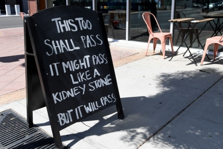 """Chalkboard sign on sidewalk reads """"This too shall pass. It might pass like a kidney stone, but it will pass."""" We take a look at whether kidney stones are more painful than childbirth."""