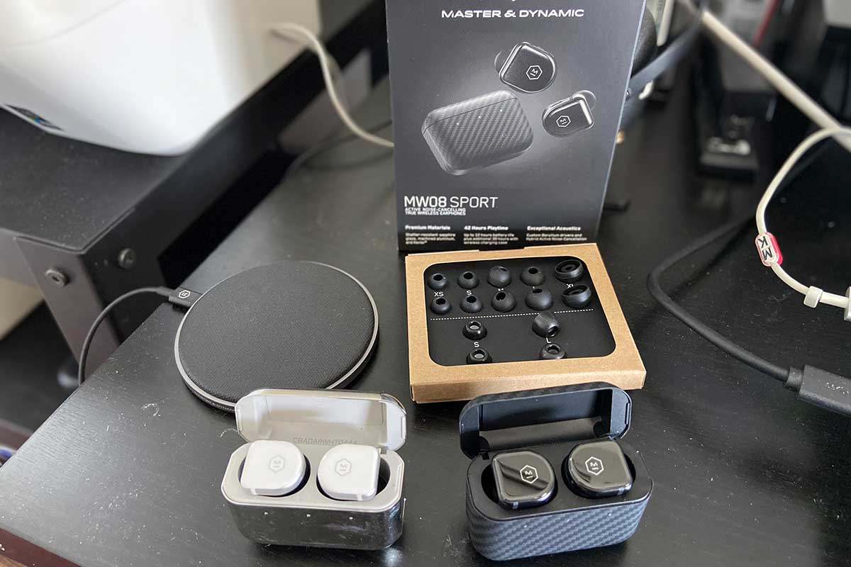 Comparing the old MW08 earbuds against the MW08 Sport (and shown with the wireless charging pad, foam and silicone tips and packaging