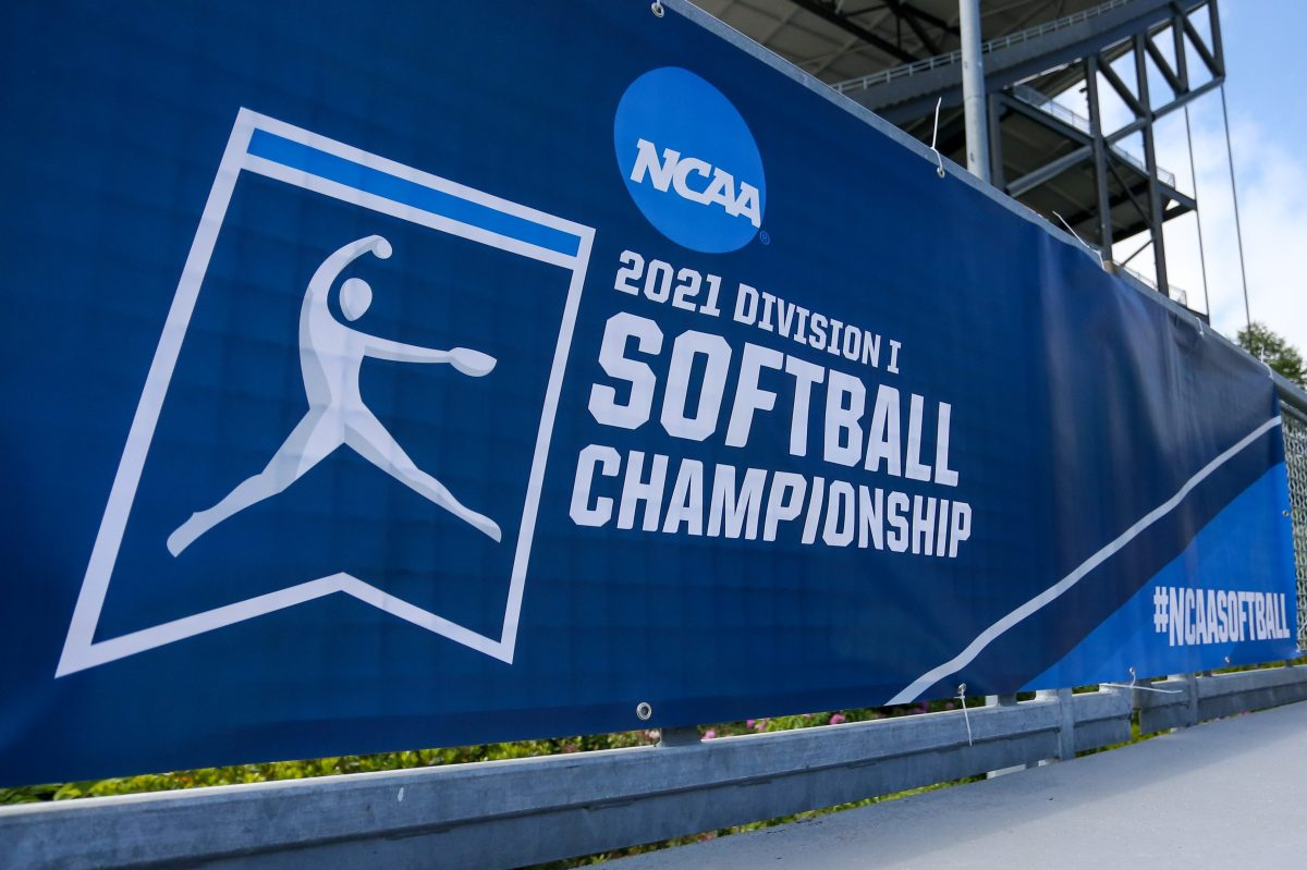 A blue and white banner for the 2021 Division I Softball Championship with the NCAA logo at a game