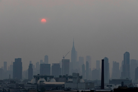 Manhattan skyline and a red sun is seen in a thick haze in New York, the United State, July 20