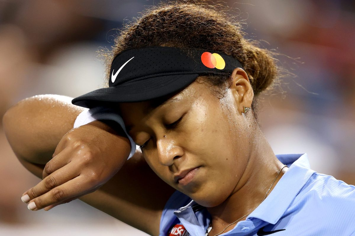 Tennis star Naomi Osaka of Japan wipes her face while playing. Her mental health struggles have led to the US Open enacting new procedures for the 2021 tournament.