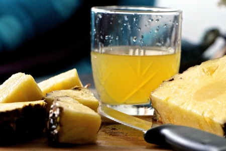 Glass of pineapple juice on table with sliced pineapple
