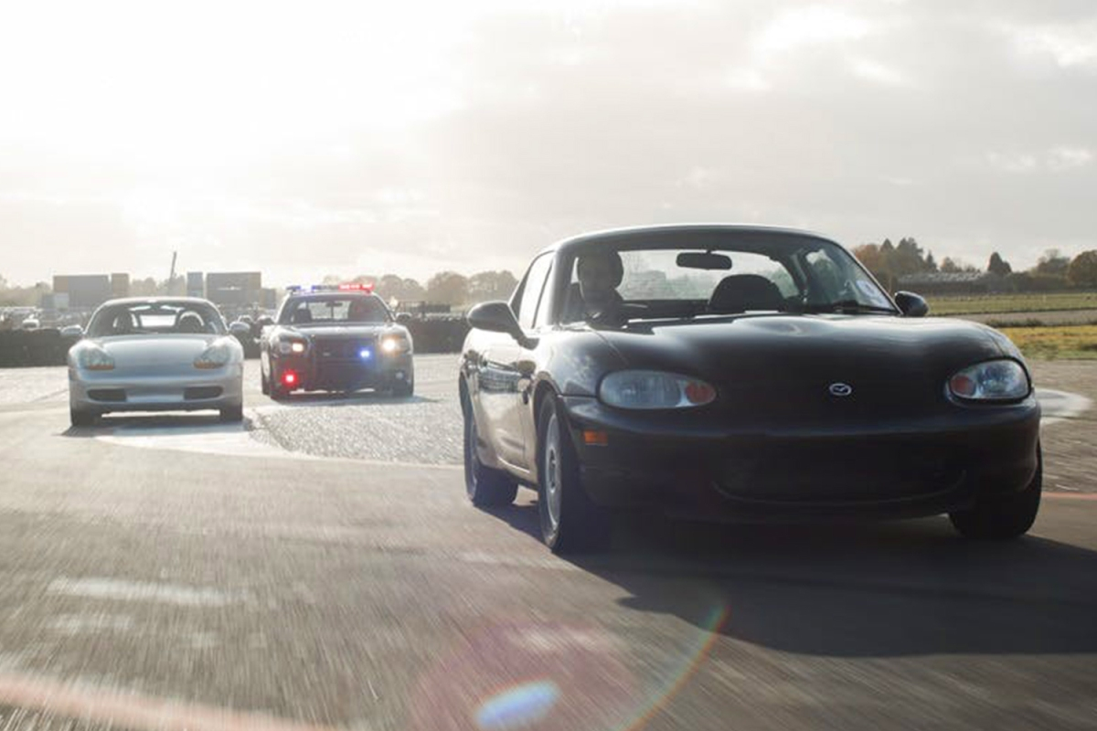 A Mazda MX-5 Miata and Porsche Boxster being chased by a Dodge Charger Police Interceptor. Ever wanted to try outrunning the police? Trackdays offers you the chance to try.