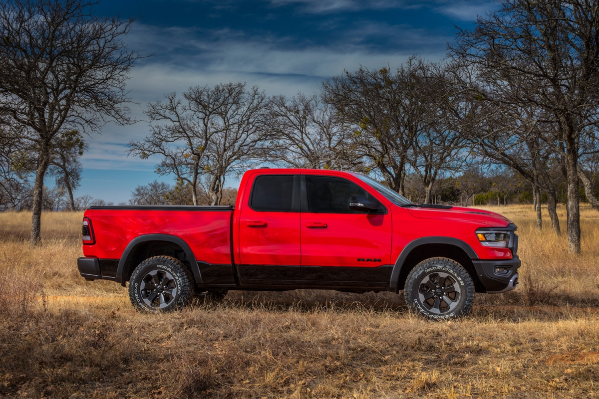 A profile view of a red Ram Trucks 1500 Rebel pickup sitting in the grass in front of a line of trees