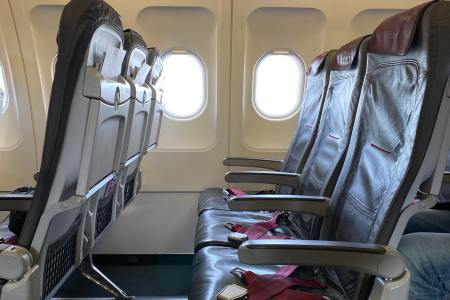 A row of three empty airplane seats without passengers in a commercial airliner with light coming in through the open windows