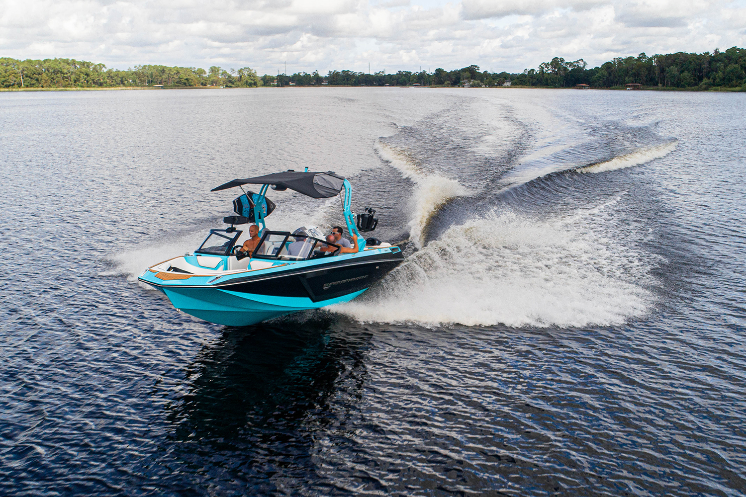 The Super Air Nautique GS22E electric wakesurfing and wakeboarding boat cruising on a lake. Correct Craft launched the all-electric towboat in 2020.
