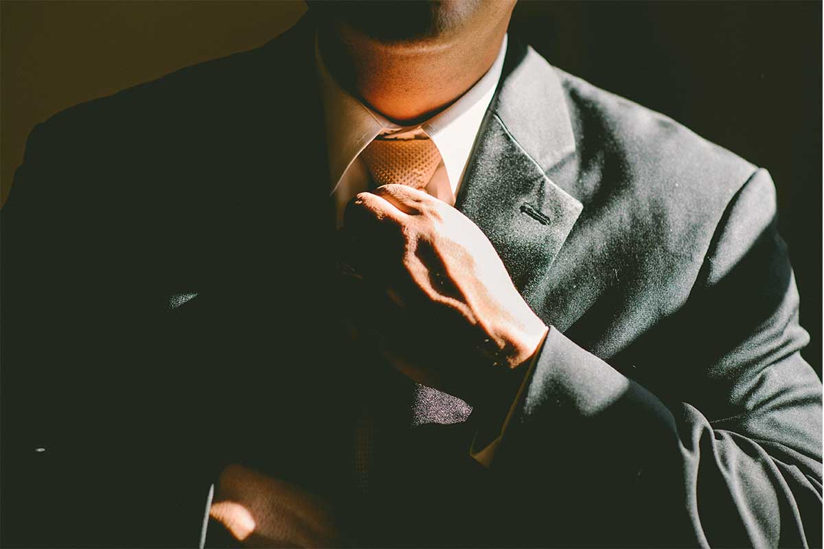 A man in the shadows loosening his tie. A tight tie has been linked to a myriad of health issues.
