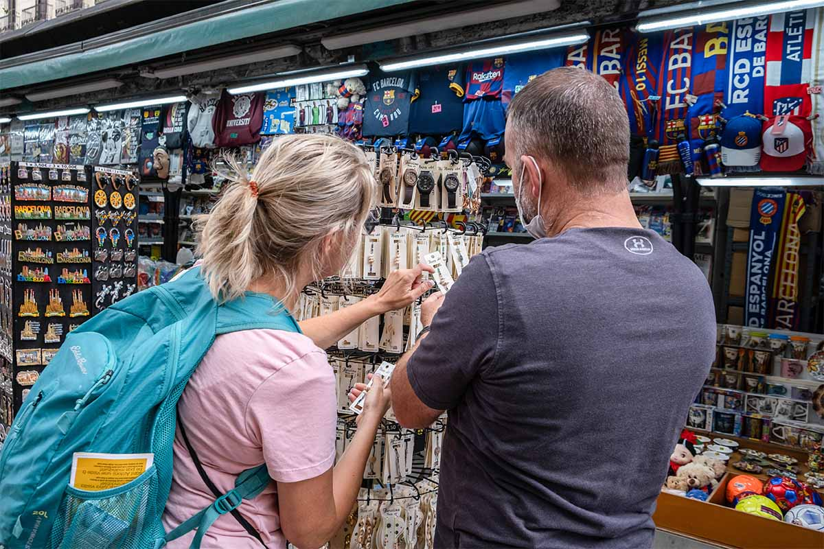 Two tourists are seen buying souvenirs at one of the traditional newsstands on La Rambla. The economic balance of the economic sectors that depend on tourism closed in August below expectations due to the persistent mobility restrictions derived from the so-called fifth wave of Covid.