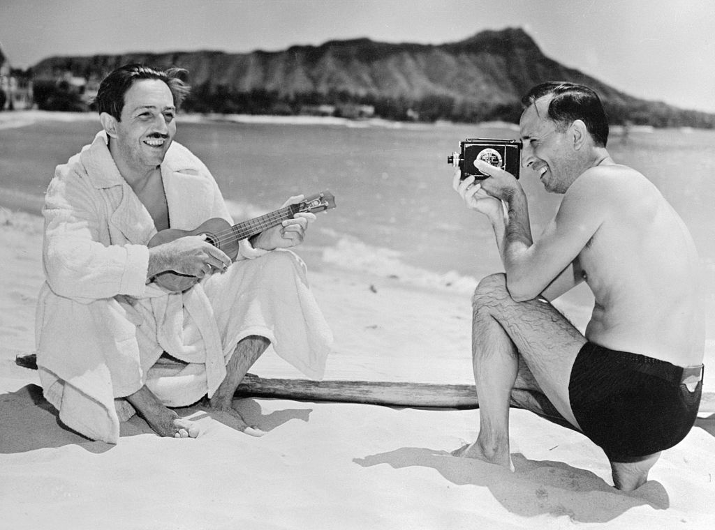 Walt and Roy Disney on the beach in a black and white photo. The brothers' first house in Los Angeles is undergoing a restoration.