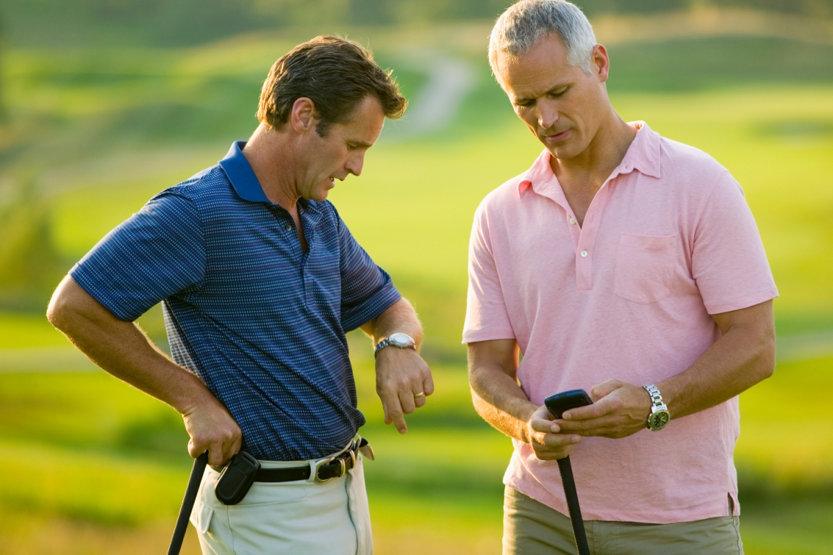 two men stand on golf course, one checking his watch, the other looking at his phone. Some lady robbers have been stealing Rolexes from golfers recently.
