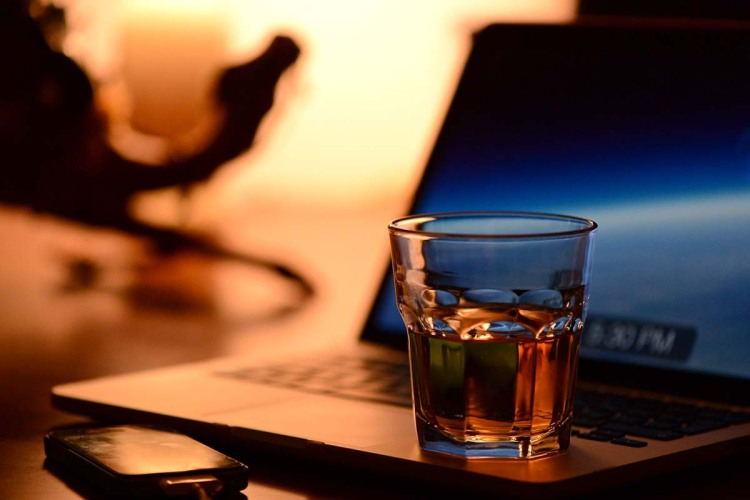 Whiskey, laptop and a smartphone on a desk. Whisky investment is entering the digital space.