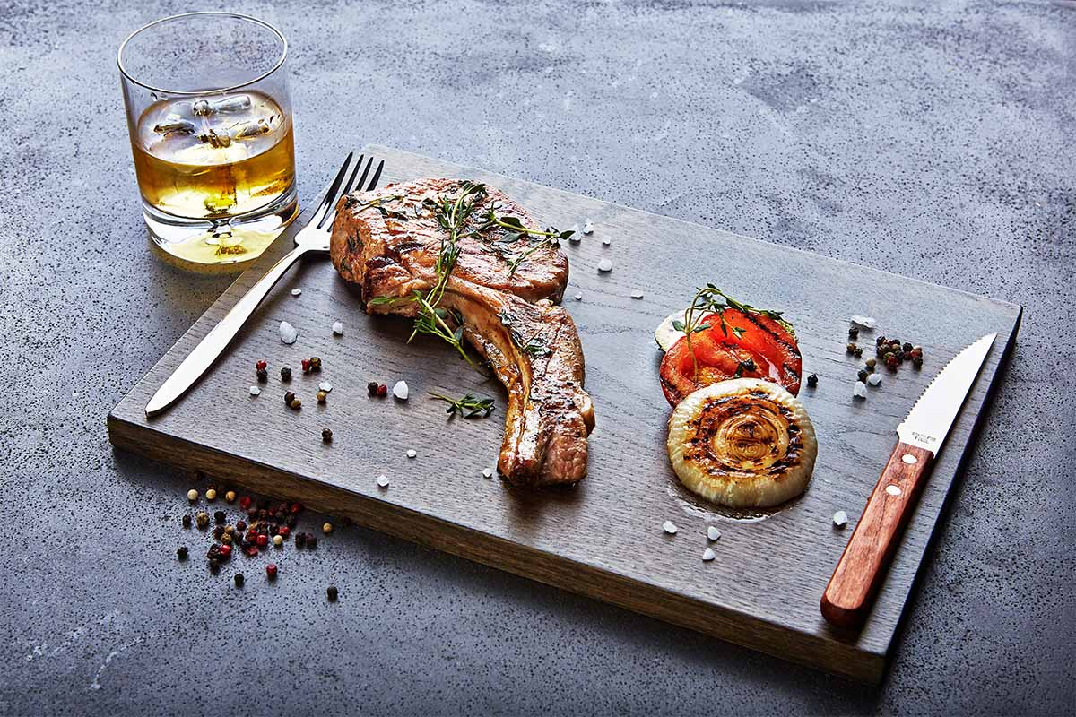 A piece of steak on a tray with a whiskey to the side. Besides combining with food pairings, whiskey is also good for cooking.