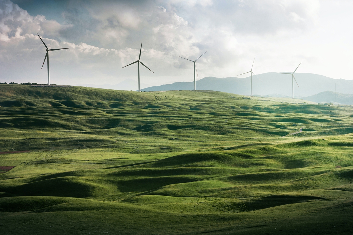 Wind turbines on hills above green fields. What would happen if we switched to green energy and stopped emissions today?