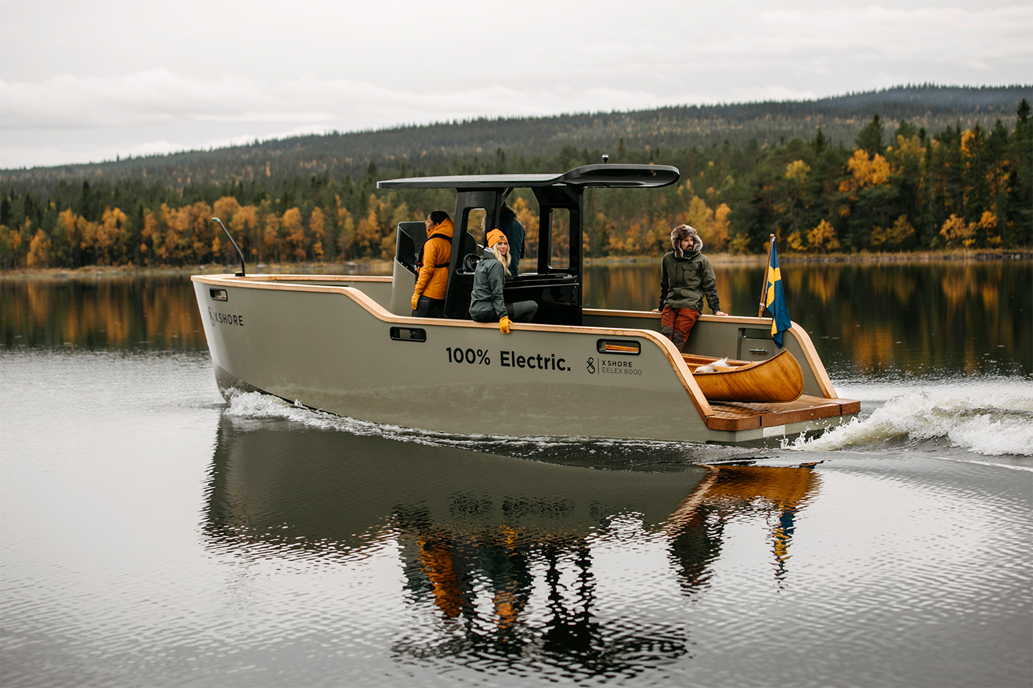 The 100% electric Eelex 8000 from X Shore slowly gliding through still water with fall foliage in the background. The Swedish electric boat builder hopes to be a leader in the industry.
