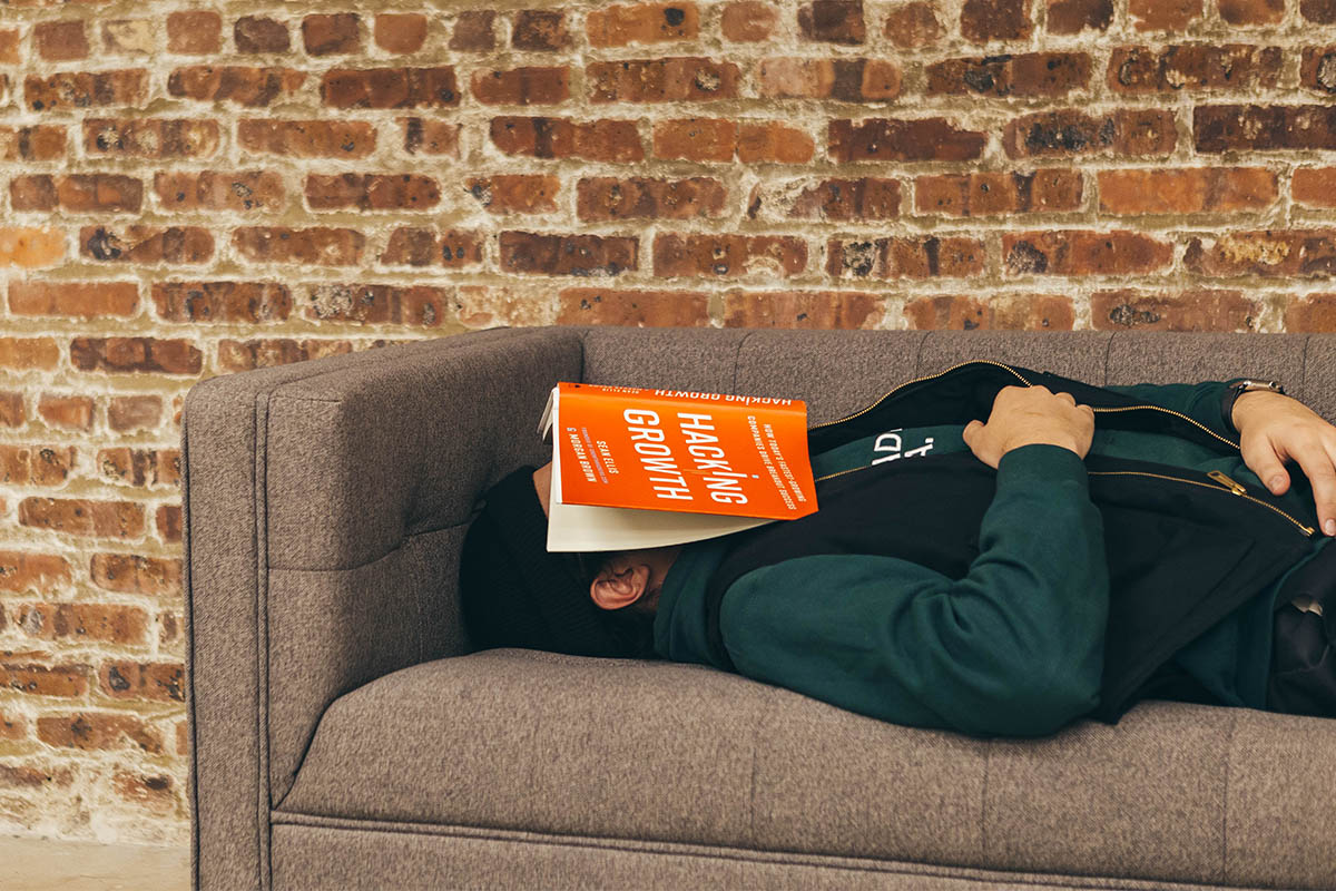 A man lies on the couch with a book over his face