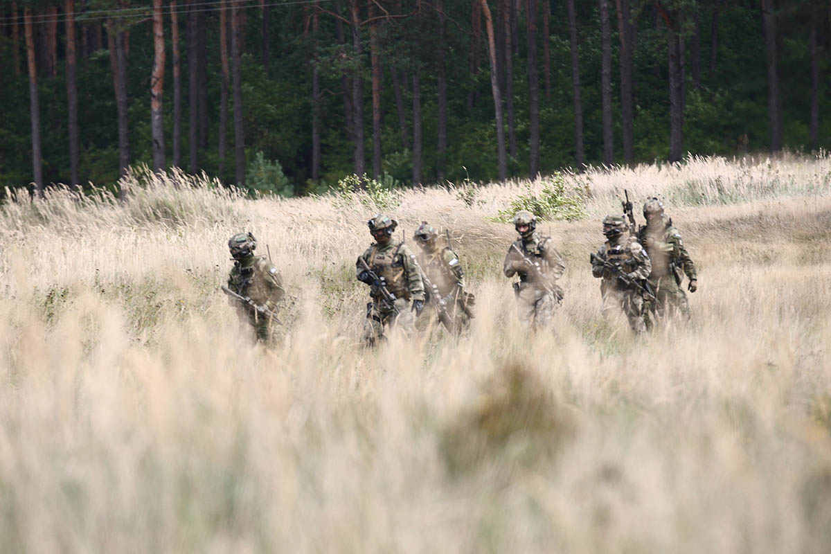 Special forces troops march through a field.