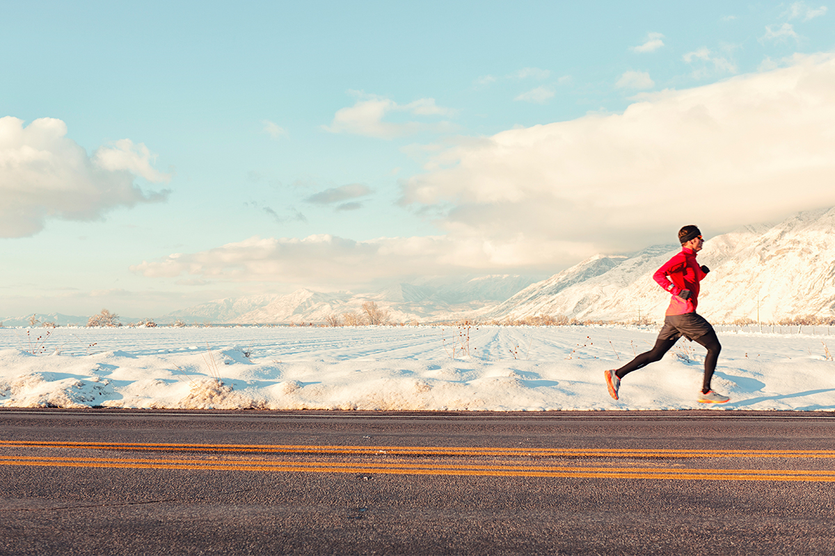A man running past snowy mountains.