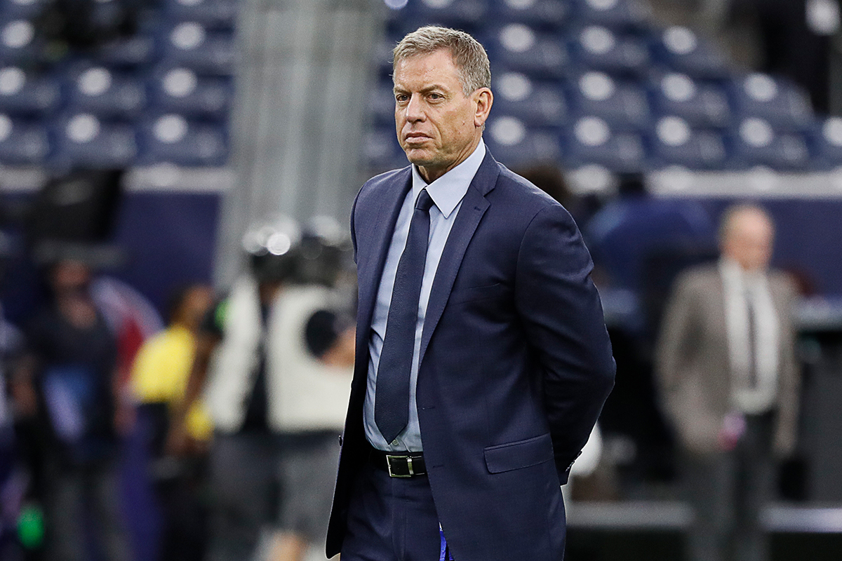 Former NFL quarterback Trok Aikman standing on a football field in a suit before a game