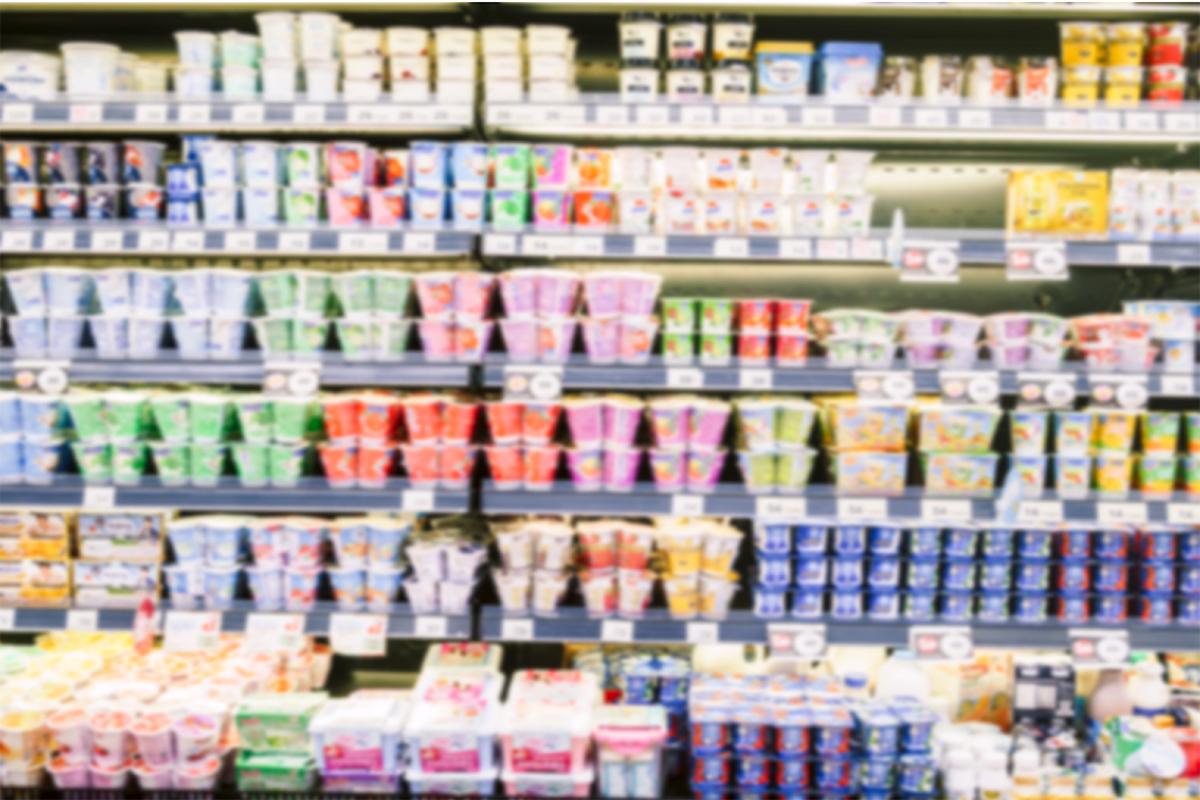 A blurry yogurt aisle in a grocery store.