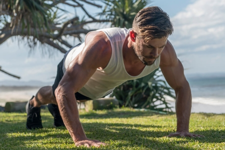 Chris Hemsworth performs a push-up on the grass.