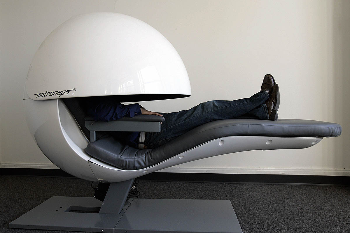 A man sleeps in a futuristic nap pod.
