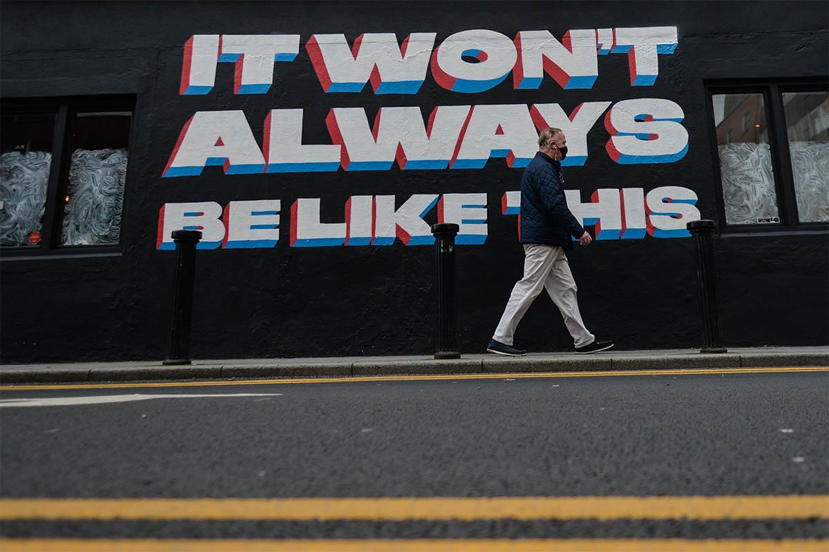 A man walks past a COVID sign in Dublin.
