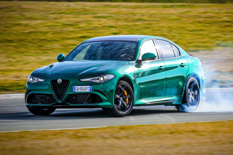 A green 2021 Alfa Romeo Giulia Quadrifoglio sport sedan smoking its tires on a racetrack surrounded by grass