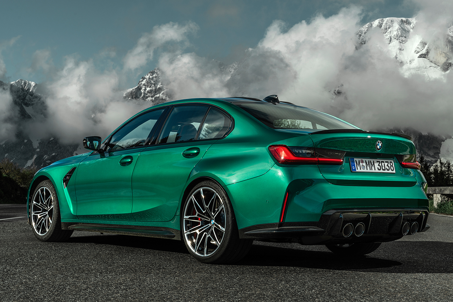 The new BMW M3 Competiton Sedan in green sits on the road with snow-capped mountains covered in clouds in the background