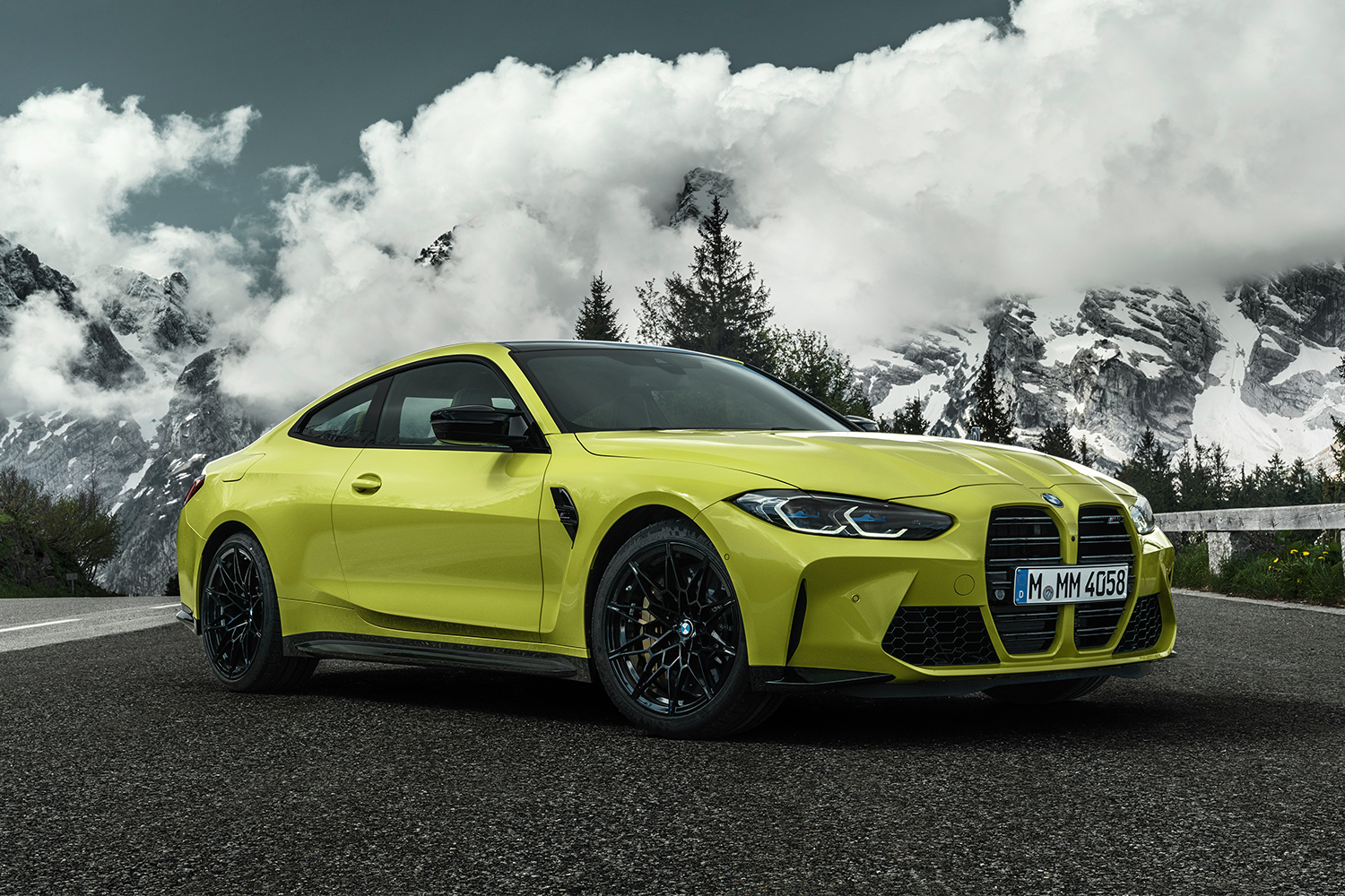 The new BMW M4 Competition Coupé in yellow sits still on the road with snowy mountains and trees at the cloud line in the background