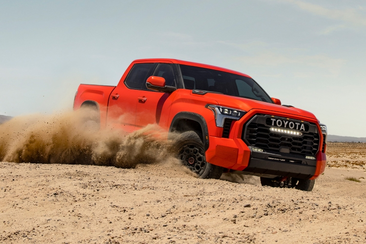 The new 2022 Toyota Tundra pickup in the color Solar Octane driving through the sand and kicking up dirt