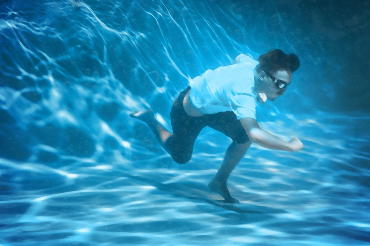 A man in goggles runs on the surface of a pool.