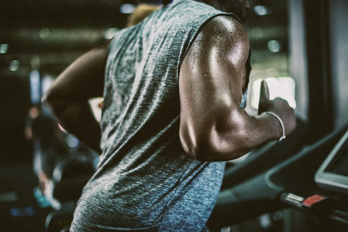 A sweaty man in a sleeveless shirt runs on a treadmill.