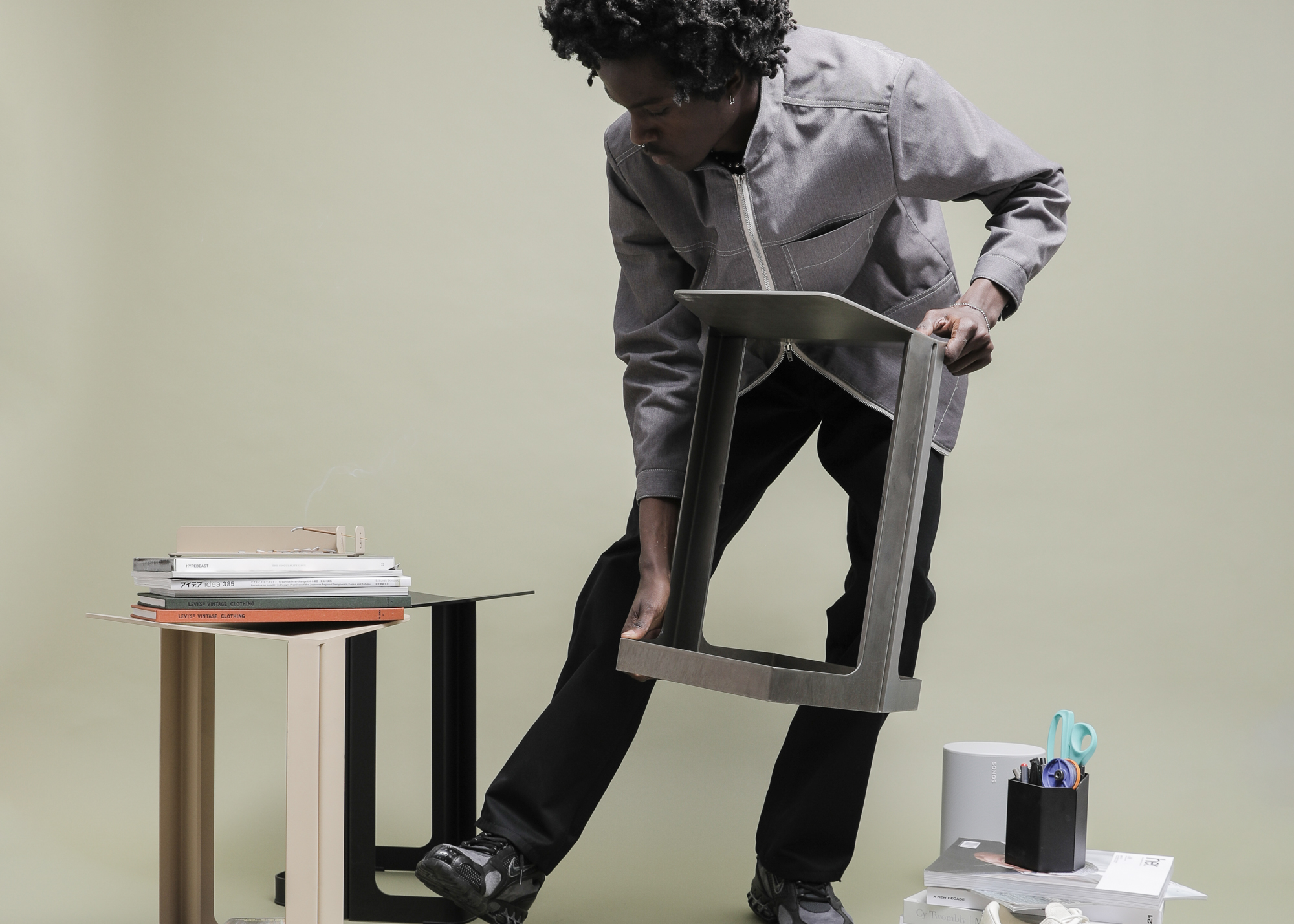 A man lifts up the new sheet metal stool from Oakland design company BASE