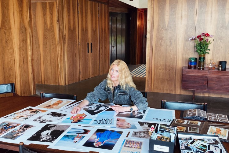 """Supermodel Claudia Schiffer sitting at a table featuring dozens of fashion photographs from the 1990s, some of which will go into her exhibit """"Captivate!"""" and accompanying coffee table book"""