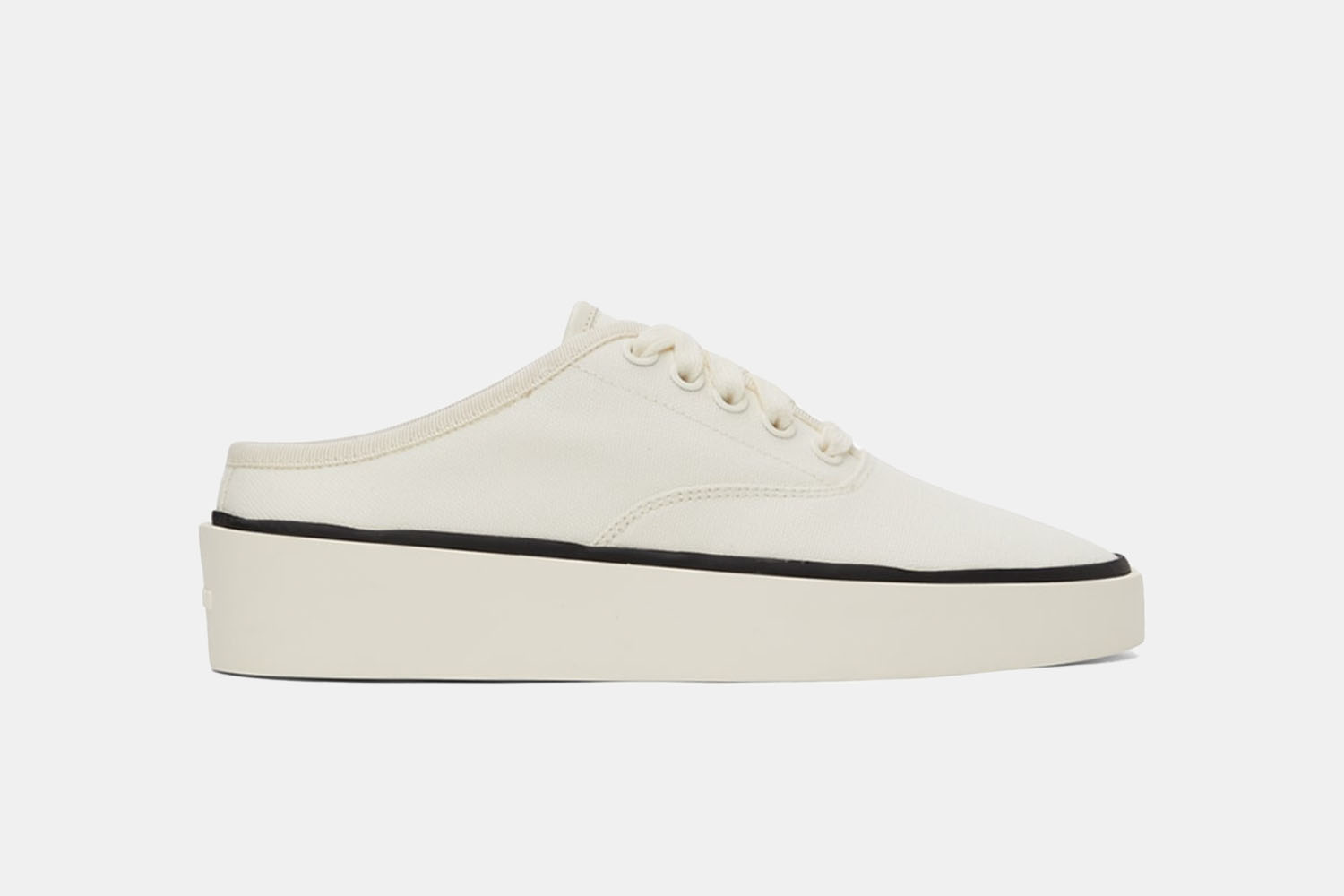 a all white sneaker with navy accents and a mule-style back.