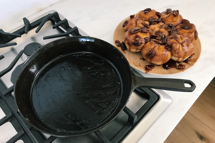 The No. 8 cast iron skillet from Field Company sitting on a stovetop next to a plate of pecan sticky buns on a white countertip