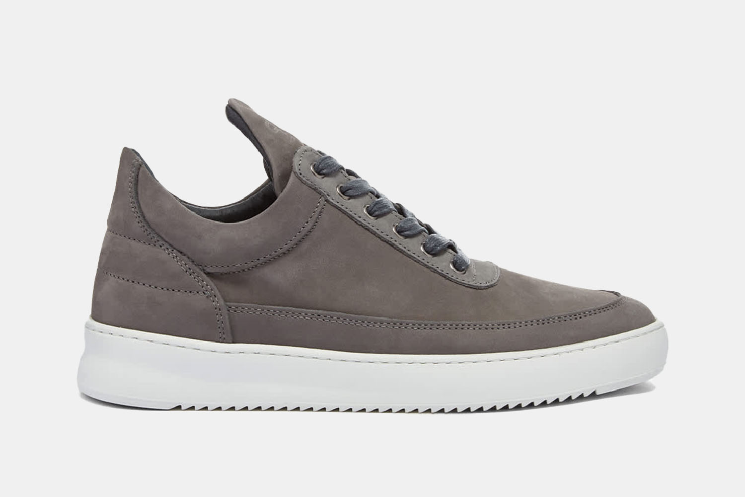 A suede grey sneaker with a white sole.