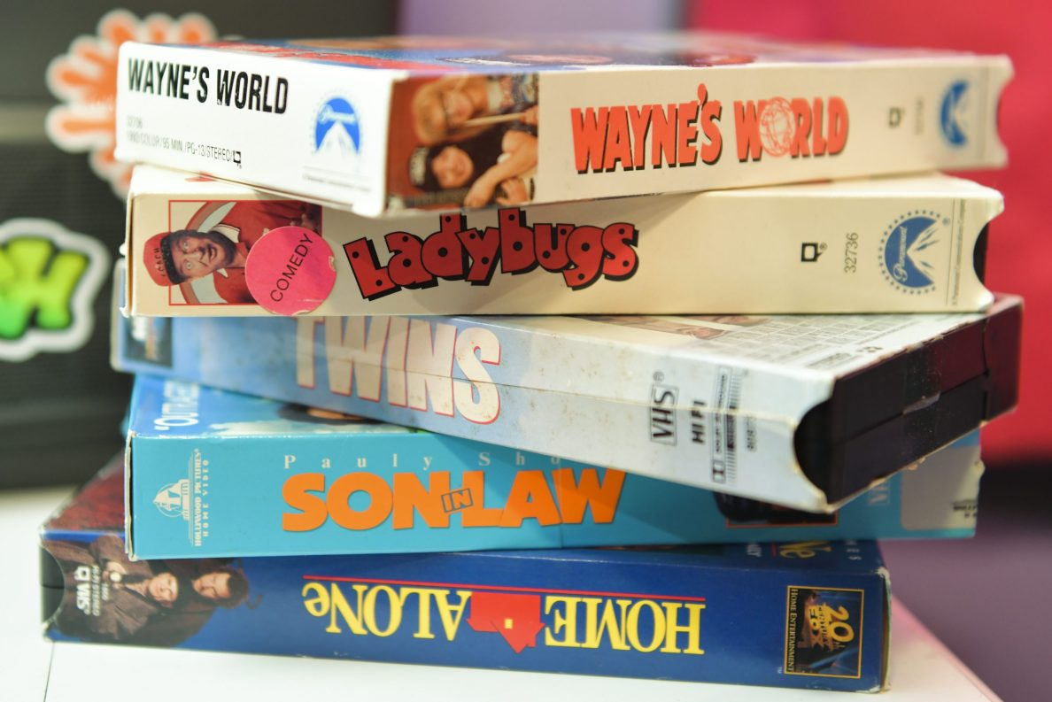 A stack of retro VHS tapes including Wayne's World, Ladybugs, Twins, Son in Law and Home Alone