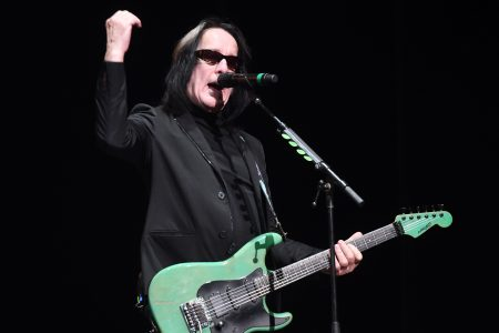 Todd Rundgren wearing sunglasses and holding a mint green guitar performs onstage during the 50th anniversary tribute tour celebrating The White Album at The Wiltern on December 11, 2019 in Los Angeles, California