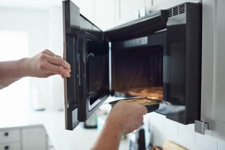 Unrecognizable male putting food into a microwave