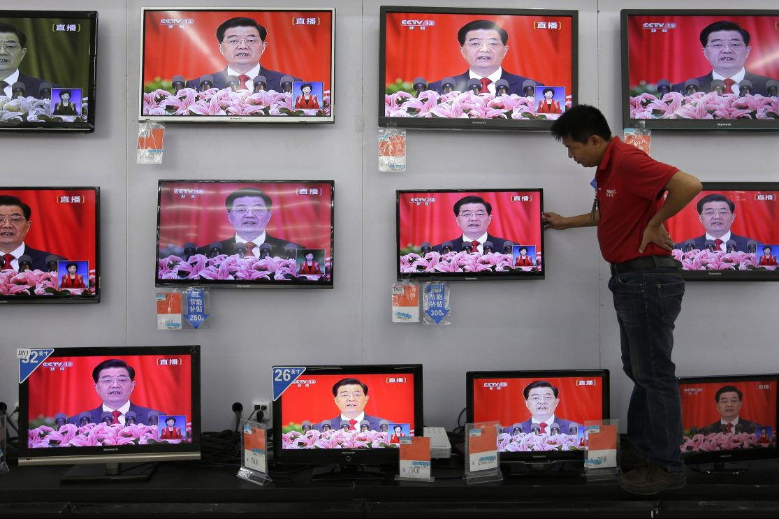 A man adjusts a television screen showing a live broadcast of former Chinese president Hu Jintao speaking at the opening of the 18th Communist Party Congress, at a supermarket in Wuhan, central China's Hubei province on 8 November 2012.