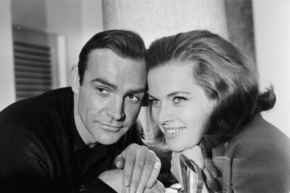 """A black and white photo of Sean Connery (James Bond) and Honor Blackman (Pussy Galore) promoting the film """"Goldfinger"""" in 1964"""