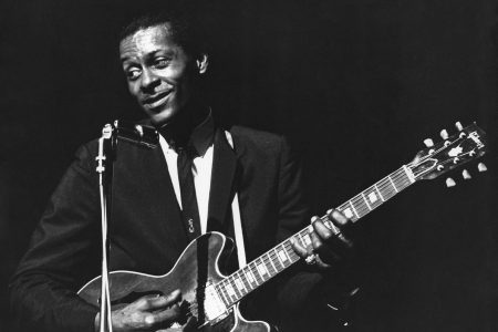 Chuck Berry performs onstage with his Gibson hollowbody electric guitar circa 1965.