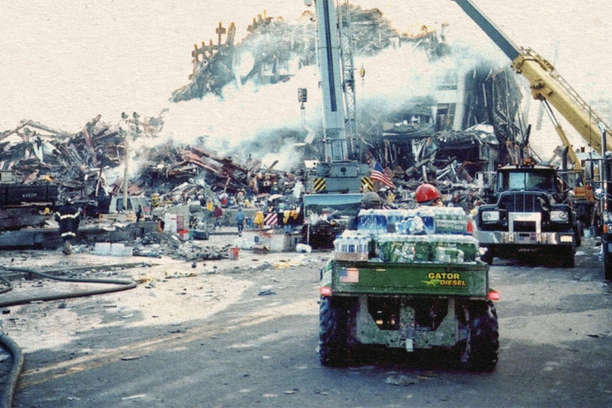 A green John Deere Gator utility vehicle loaded with packs of bottled water facing Ground Zero in the aftermath of the 9/11 terror attacks in New York City, the collapsed towers still on fire and smoking