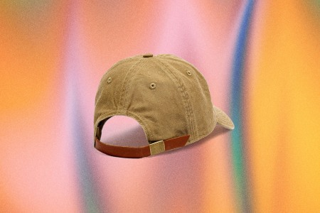 A light brown backwards baseball cap from Madewell on a multi-colored backdrop